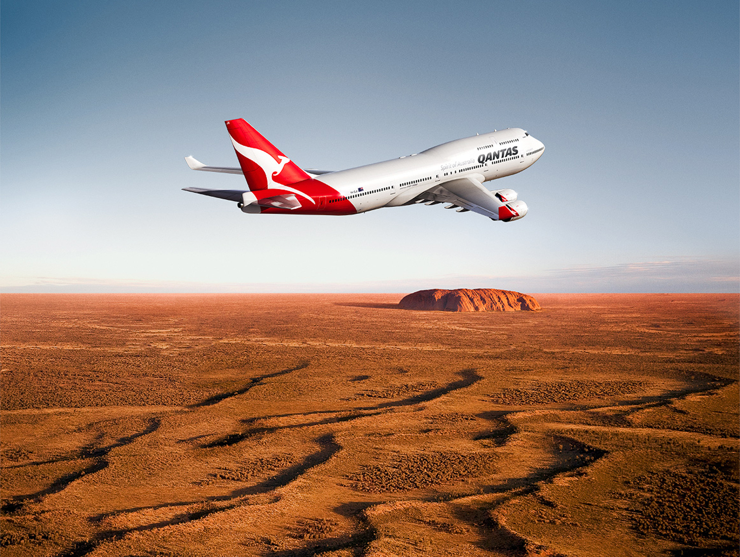 Qantas flying over Northern Territory outback with Ayres rock in background