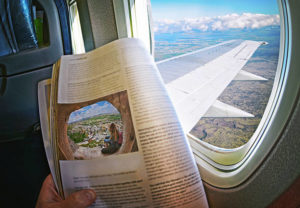 Woman Is Sitting By Window On A Plane With an inflight magazine