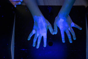 UV light revealing the germs on hands and surfaces