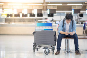 Young man waiting for check in and drop his luggage at airline check-in counter of international airport terminal