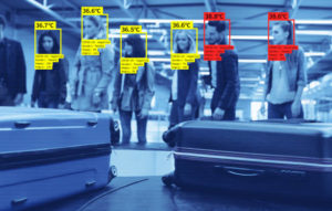 Facial recognition system at the airport during covid-19 pandemic, measuring temperature. People waiting for luggage.