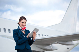 Image of a flight attendant standing in front of an aircraft and using a digital tablet.