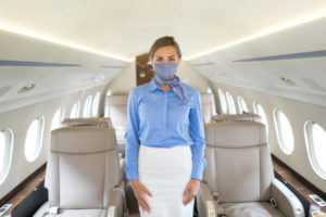 Flight attendant in a private airplane wearing a facemask to avoid an infectious disease