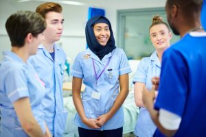 four young medical staff members chat to each other and their manager after a shift on the wards.