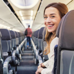 Young woman smiles while waiting to exit a commercial flight. A male passenger is exiting in the background.