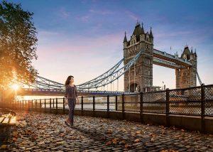 A cinematic shot: The Singapore Girl walking along London's Tower Bridge