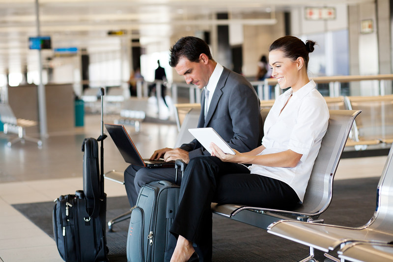 A business man and a business woman wait in an airport lounge ready to board a flight