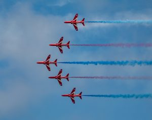 The Red Arrows flying in unison at an air show display leaving a trail of red, white and blue