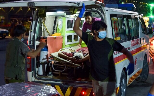 Medical staff bring an injured man to a hospital in an ambulance after two powerful explosions outside the airport in Kabul