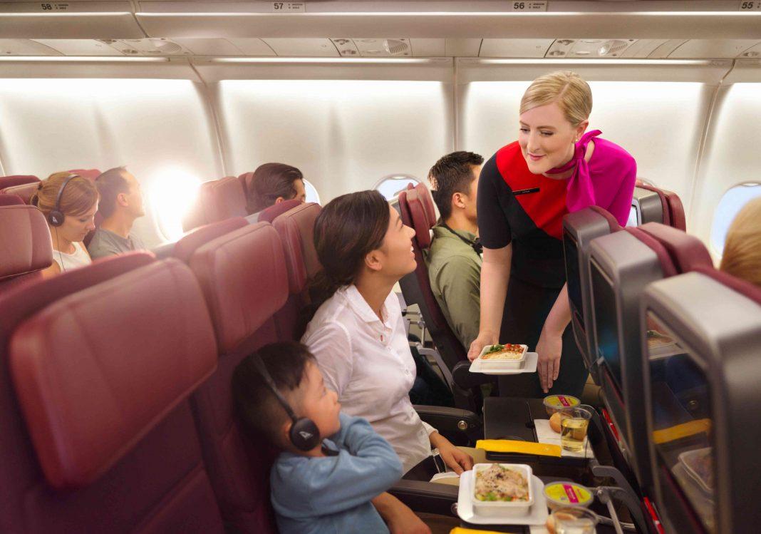 Showing Qantas air hostess providing customer service