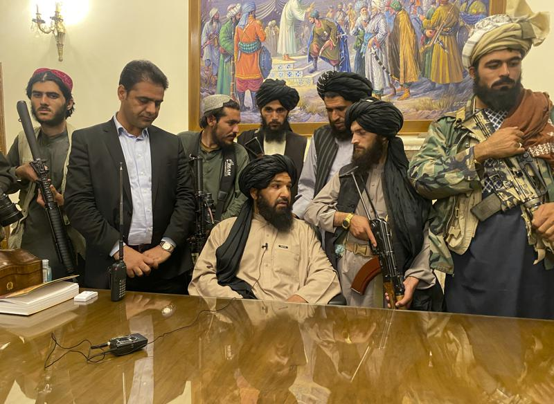 Showing Taliban insurgent's gathered at the end of a table